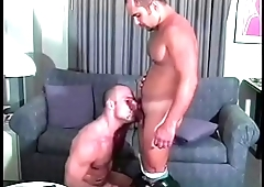 Hunk cop sits on the couch and takes large cock down his throat